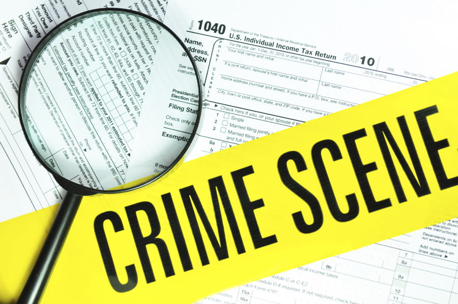 Crime scene tape and magnifying glass over 1040 tax forms