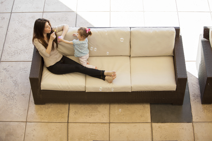 Woman blowing bubbles on couch with child