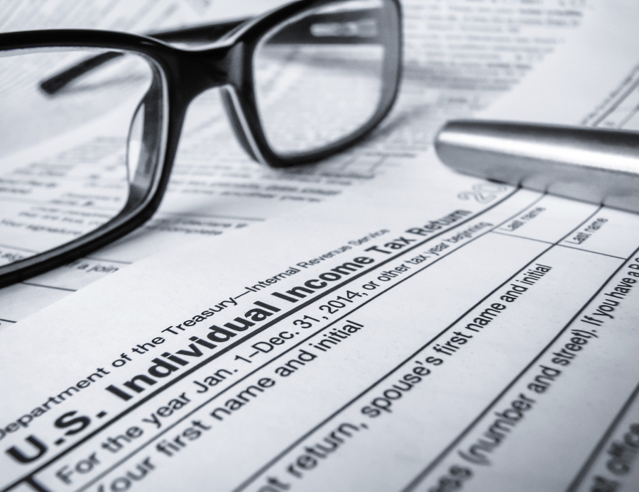 glasses and pen laying on top of tax form