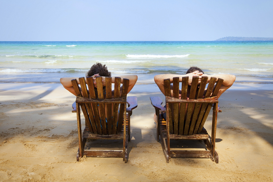 Couple sitting in chairs relaxing on the beach
