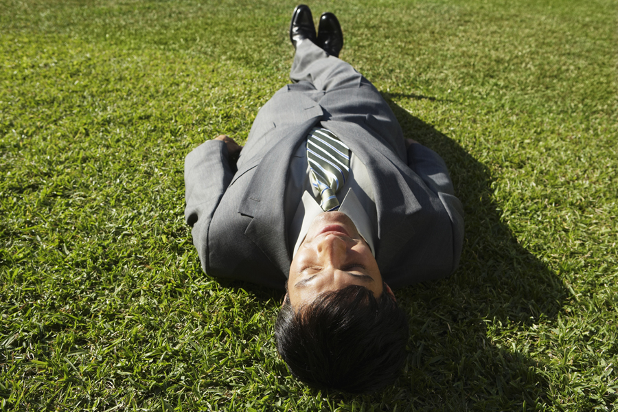 man laying on grass relaxed
